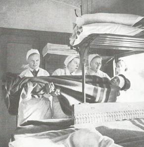 Rintamalla haavoittuneita kuljetettiin junavaunuissa, joissa lotat olivat avustustehtävissä.