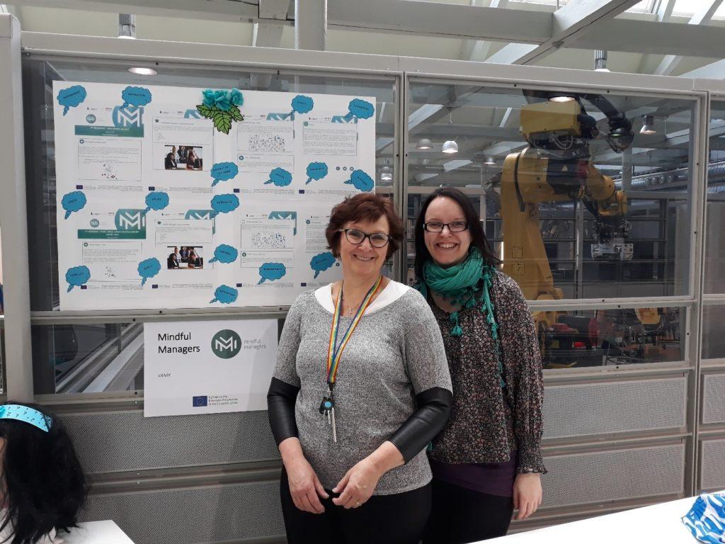 Kuvassa seisovat hanketyöntekijät Suvi Kallio ja Sanna Saikkonen kuvataulun edessä Eurooppa-päivänä keväällä 2019 Technobotniassa.