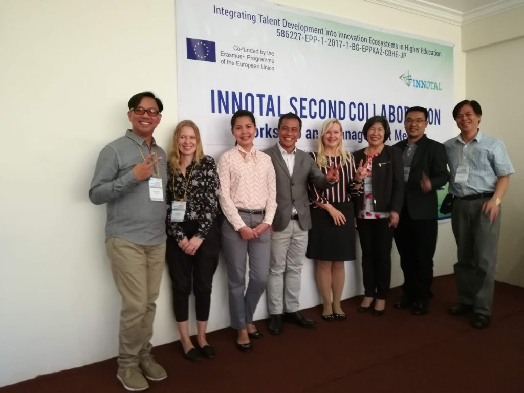 """Group of people standing in front of the big sign that reads """"Innotal second collaboration""""."""